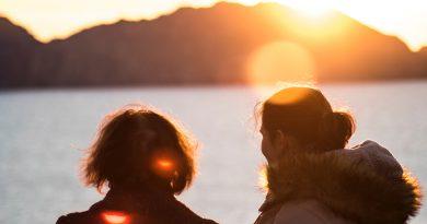 Doua femei pe malul marii in apus.